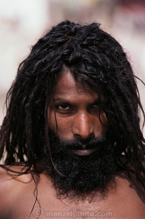 Portrait of a naga who has been smoking hash at Kumbh Mela.  Every 12 years, millions of devout Hindus celebrate the month-long festival of Kumbh Mela by bathing in the holy waters of the Ganges at Hardiwar, India. Hundreds of ashrams set up dusty, sprawling camps that stretch for miles. Under the watchful eye of police and lifeguards, the faithful throng to bathe in the river.