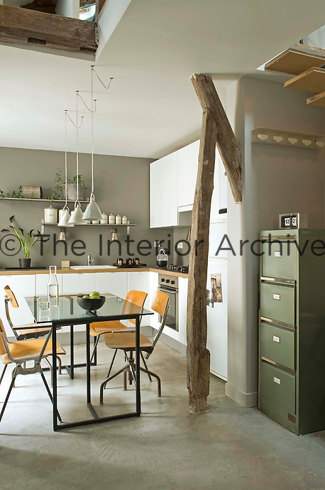 An ancient beam acts as a discreet room divider between the office and kitchen-diner in the open plan loft; the dining table is a sheet of glass on metal trestles and around it are antique office chairs