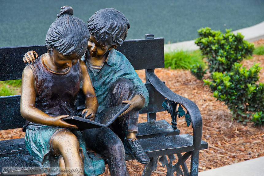 The gorgeous sculpture of two children reading a book on a park bench at Stanton Central Park's children's play area, seen on a rainy day with mulch and plants in the background.  The children are covered in raindrops.`