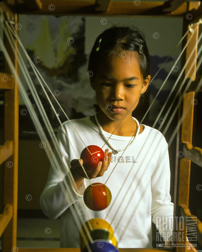 Young girl experiments with concepts of motion and reaction, using billiard-type colored balls at science center
