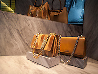 Leather handbags in the window of a Prada store in New York on Tuesday, June 16, 2015. Luxury goods makers such as Prada, Louis Vuitton and Gucci are seeing a shift in buying habits from conspicuous high-end fashion to more unique, logo-less and bespoke purchases. (© Richard B. Levine)