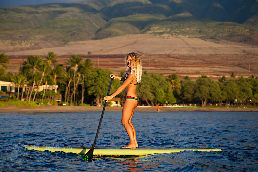 Surf instructor Tara Angioletti on a stand-up paddle board off Canoe Bearch, Maui. Hawaii.  Image is model released.