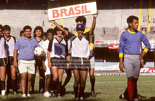 Rio de Janeiro, Brazil. Brazil youth team in black and white strip holding sign 'Brasil'; Maracana football stadium.