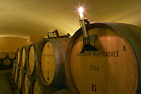 The old style vaulted barrel aging cellar with barriques pieces with maturing wine. A burning candle on a barrel stamped with Chassagne-Montrachet 2004 used for controlling if a racked wine is clear or cloudy, Maison Louis Jadot, Beaune Côte Cote d Or Bourgogne Burgundy Burgundian France French Europe European