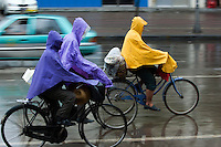 Men wearing raincoats while riding their bikes in the rain, Datong, Shanxi, China.