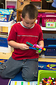MR / Schenectady, NY. Zoller Elementary School (urban public school). Kindergarten inclusion classroom. Student (boy, 5) plays with interconnecting blocks at math learning center time. MR: Gia3. ID: AM-gKw. © Ellen B. Senisi.