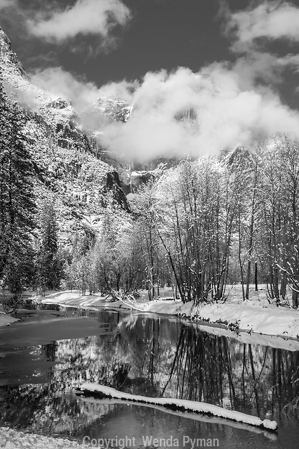 Clearing storm by the Merced River, framed by dramatic clouds and a fallen log.