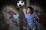 A young boy plays street soccer against a graffiti covered wall - with dramatic lighting and subdued colors - EXCLUSIVELY on ALAMY - http://www.alamy.com/stock-photo-a-young-boy-plays-street-soccer-against-a-graffiti-covered-wall-with-67184257.html