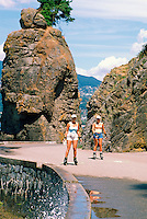 Stanley Park, Vancouver, BC, British Columbia, Canada - Siwash Rock and Women rollerblading on Seawall along English Bay