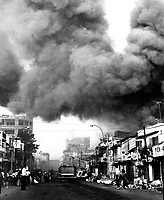 Black smoke covers areas of the capital city and fire trucks rush to the scenes of fires set during attacks by the Viet Cong during the festive Tet holiday period.  Saigon, 1968.  (USIA)<br /> EXACT DATE SHOT UNKNOWN<br /> NARA FILE #:  306-MVP-25-2<br /> WAR &amp; CONFLICT BOOK #:  418