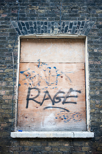 "London, England. ""rage"" written on a boarded up window in an old, cracked brick wall."