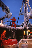Deckhands beat ice off the railing while crab fishing in the Bering Sea onboard the F/V Maverick.