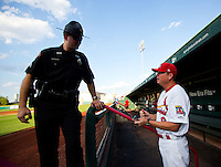 Manager Mike Shildt (8) of the Springfield Cardinals talks with a member of the Greene County Sheriff prior to a game against the Arkansas Travelers at Hammons Field on July 25, 2012 in Springfield, Missouri. (David Welker/Four Seam Images)