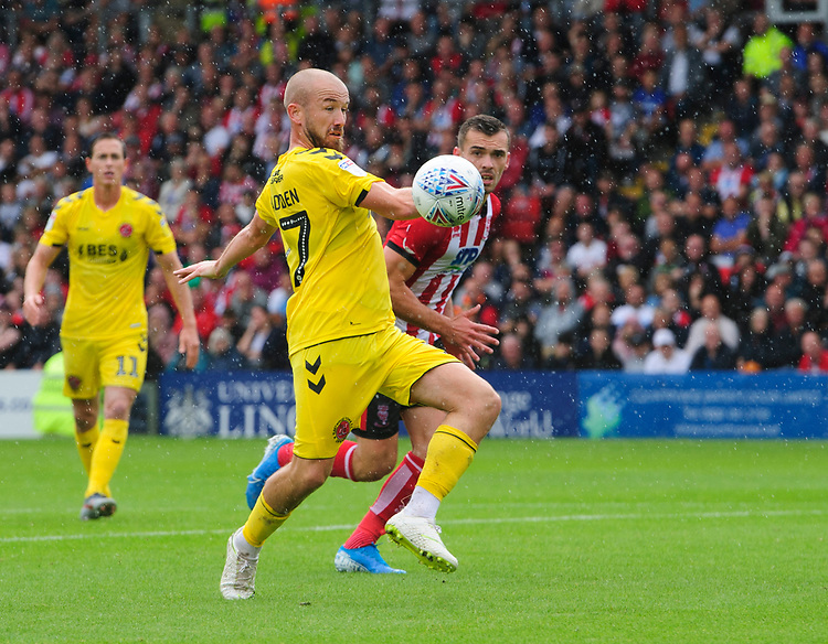 Fleetwood Town's Paddy Madden under pressure from Lincoln City's Harry Toffolo<br /> <br /> Photographer Chris Vaughan/CameraSport<br /> <br /> The EFL Sky Bet League One - Lincoln City v Fleetwood Town - Saturday 31st August 2019 - Sincil Bank - Lincoln<br /> <br /> World Copyright © 2019 CameraSport. All rights reserved. 43 Linden Ave. Countesthorpe. Leicester. England. LE8 5PG - Tel: +44 (0) 116 277 4147 - admin@camerasport.com - www.camerasport.com