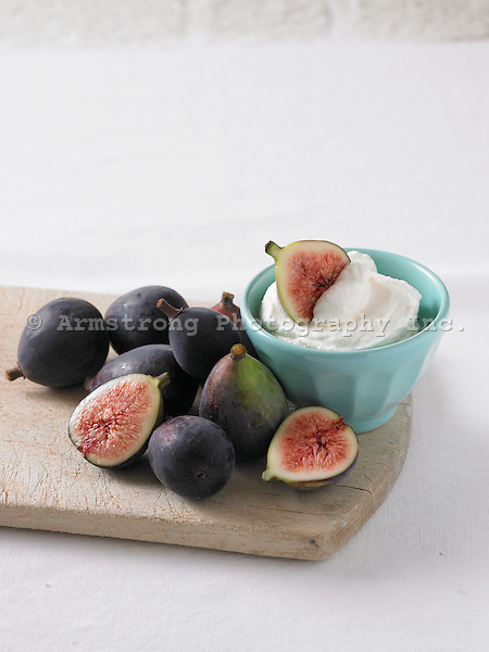 Figs and yogurt on a cutting board