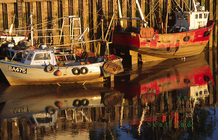 Small fishing boats reflected in the River Dee at Kirkcudbright Galloway Scotland UK