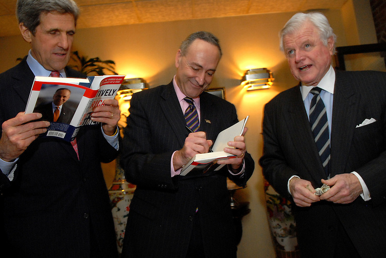 "Sen. Chuck Schumer, D-N.Y., center, signs his new book ""Positively American"" for Sen. Ted Kennedy, D-Mass., right, as Sen. John Kerry, D-Mass., reads a portion, at a book signing reception at the Hunan Dynasty on Capitol Hill, Tuesday, January 30, 2007."