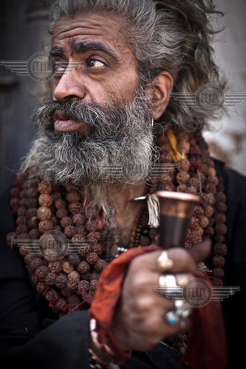 A sadhu, sitting outside the Pashupathinath Temple, smokes marijuana in a chilum outside the Pashupathi Nath Temple.