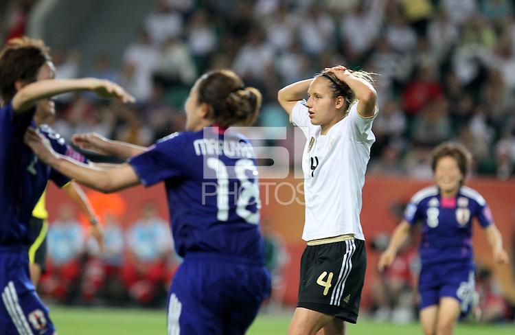 Wolfsburg , 100711 , FIFA / Frauen Weltmeisterschaft 2011 / Womens Worldcup 2011 , Viertelfinale ,  Deutschland (GER) - Japan (JPN) .Babett Peter (GER) enttäuscht , Japan jubelt nach dem 1:0 durch Torjubel Karina Maruyama (JPN)  .Foto:Karina Hessland .