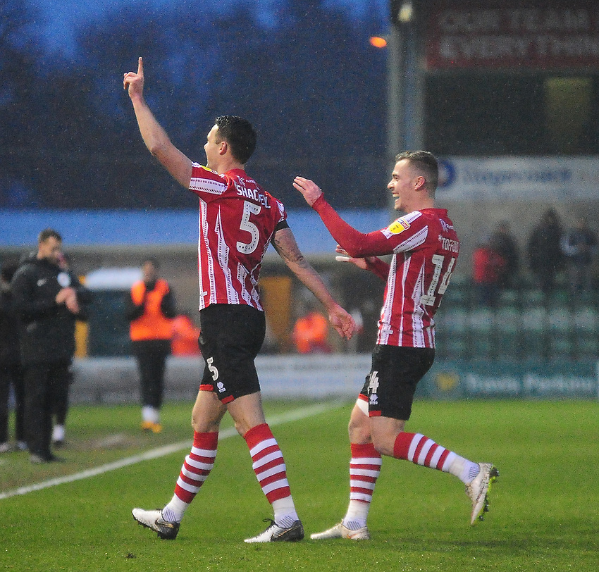 Lincoln City's Jason Shackell, left, celebrates scoring his side's third goal with team-mate Harry Toffolo<br /> <br /> Photographer Andrew Vaughan/CameraSport<br /> <br /> The EFL Sky Bet League Two - Saturday 15th December 2018 - Lincoln City v Morecambe - Sincil Bank - Lincoln<br /> <br /> World Copyright © 2018 CameraSport. All rights reserved. 43 Linden Ave. Countesthorpe. Leicester. England. LE8 5PG - Tel: +44 (0) 116 277 4147 - admin@camerasport.com - www.camerasport.com
