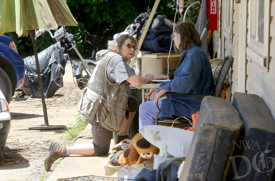 NWA Democrat-Gazette/DAVID GOTTSCHALK   Tini Kratchmer (left), a volunteer with the American Red Cross Northwest Arkansas Chapter, collects information Tuesday, May 2, 2017, from Sandy Crihfield (cq) on her front porch at the West End Apartments in Fayetteville. Rain and a swollen creek caused flooding at the Apartment causing extensive water damage inside the apartments and to personal property.
