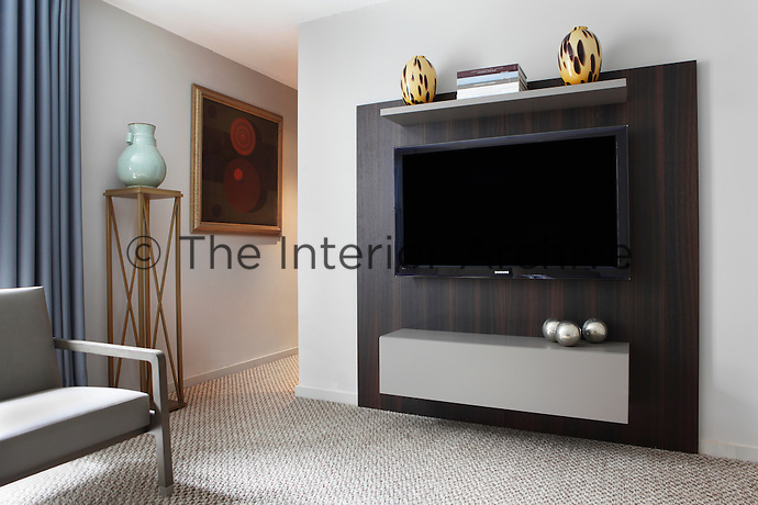A carpeted basement sitting/entertainment room with a flat screen television mounted onto a panelled wall