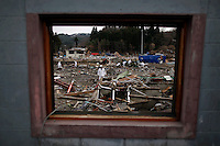 Policemen are seen through the window of destroyed house as they search for bodies of tsunami victims in Kirikiri more than two weeks after the area was devastated by a magnitude 9.0 earthquake and tsunami March 26, 2011. The March 11 quake and tsunami have left at least 27,000 dead and missing in northeast Japan.   REUTERS/Damir Sagolj (JAPAN)