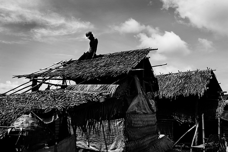 Beyond the Bullets - Preparing for Stagnation..A man replaces the roof of his shelter in an evacuation center in Datu Piang in preparation for rainy season on May 27, 2009.  These evacuees, who fled fighting last August, had initially planned to return home quickly.  But as fighting dragged on and the military continued to shell the area around their villages, they are now planning for a long stay in the evacuation centers.