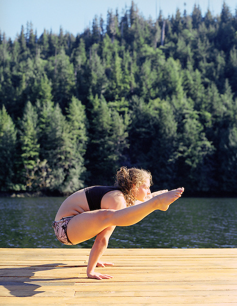 BRITISH COLUMBIA,CANADA : Nimmo Bay resort yoga instructor/massuse Jelena Lepesic practices yoga on the dock at sunset. Nimmo Bay is an angler's paradise set in the wilderness of mainland British Columbia, near the Broughton Archipelago off the northeast tip of Vancouver Island. Nimmo Bay offers spectacular scenery and access to some of the world's best salmon and trout fishing. Nimmo Bay Resort has pioneered helicopter fishing and helicopter adventures over the last 25 years. Helicopters take guests to remote coastal rivers and magical fishing holes for fabulous catch and release salmon and trout fly fishing. Nimmo Bay, British Columbia, Canada.