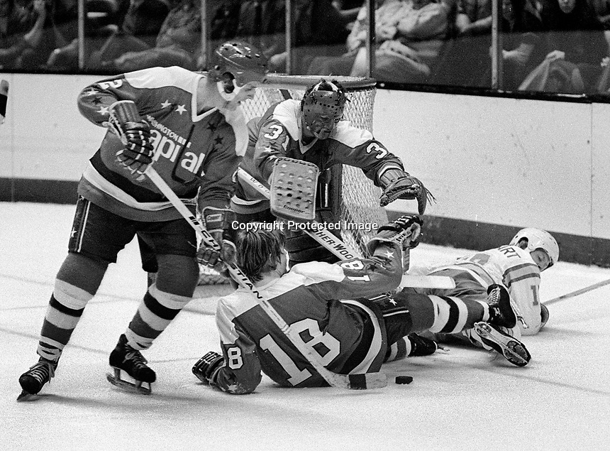 Washington Capitols Jack Lynch and #18 Rick Bragnalo helping goalie Michael Belhumer battle the Seals. (1975<br />