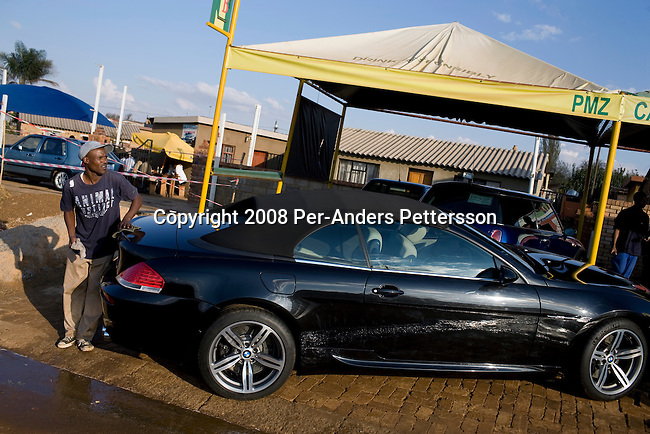 SOWETO, SOUTH AFRICA - JUNE 21:  An unidentified man washes a BMW M6 for a wealthy client at a carwash on June 21, 2008 in the Jabulani section of Soweto, South Africa. Many newly wealthy black people return to the townships during the weekends to catch up with family and friends. Many of them have left the township and live in formerly white affluent areas in the northern suburbs of Johannesburg. (Photo by: Per-Anders Pettersson/Getty Images)..