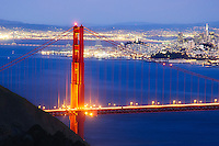 Twilight colors dazzle the north tower of the Golden gate Bridge with city lights and the Bay Bridge in the background