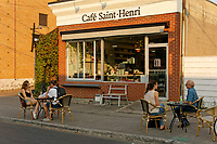 People talking at cafe table outside the Cafe Saint Henri coffee shop across from the Jean Talon Market, Montreal, Quebec Canada