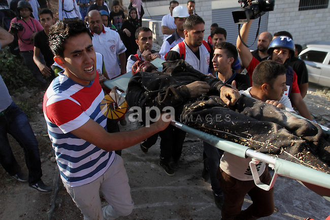 Palestinian medics carry the body of Zakariyya al-Aqra, 24, who was reportedly shot dead by Israeli soldiers, in the West Bank village of Qabalan, near Nablus on August 11, 2014. Al-Aqra was killed Monday in a shootout with Israeli forces after resisting arrest and holing up in a building in a village south of Nablus, local media reported. Photo by Nedal Eshtayah