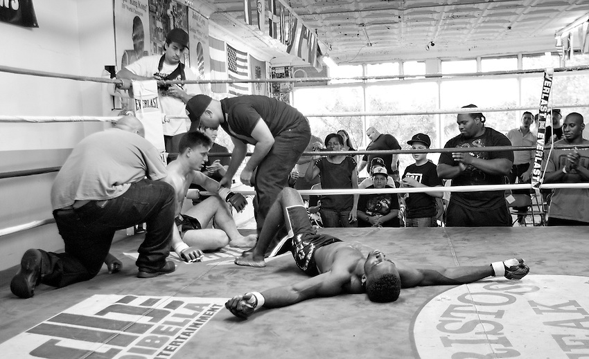 BRONX, NY - (Aug., 24, 2013) - The referee, left, and promoter Peter Storm check the condition of fighter James Funaro, who sits up after he was beaten by Jerome Mickle (right) who then collapsed after he won the main event of an unsanctioned MMA card hosted by Underground Combat League at John's Boxing Gym in the South Bronx.