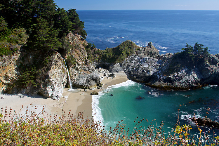 """McWay Falls in Julia Pfeiffer Burns State Park is an 80 foot waterfall that flows year-round. McWay Falls is one of only two waterfalls in the region that are close enough to the ocean to be referred to as """"tidefalls"""". It is located on McWay Creek."""