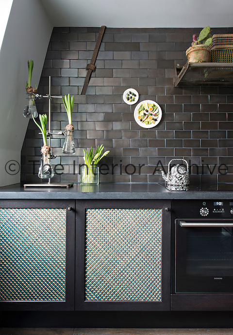 In the kitchen, a bold colour approach of black and shades of grey is offset with items in varying shades of green, such as a display of flower bulbs in a glass stand.