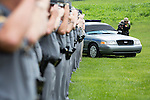 A Kentucky State Police Car with black across its windshield and lights was in the background as KSP troopers saluted.  Kentucky State Trooper Eric Keith Chrisman was laid to rest Monday June 29, 2015 in Lawrenceburg, Ky.  He died in the the line of duty June 23, 2015.  Police officers and Fire fighters from across Kentucky and the Nation came to pay respects to his family.  Photo by Mark Mahan