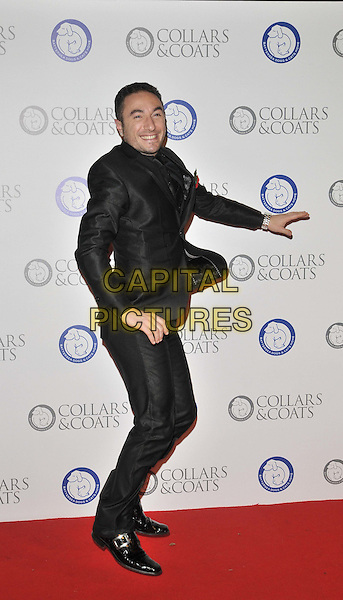 Vincent Simone.The Collars & Coats Gala Ball 2011, Battersea Evolution, Battersea Park, London, England..November 11th, 2011.full length black suit side smiling .CAP/CAN.©Can Nguyen/Capital Pictures.