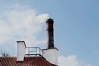 smoke coming out of a red brick chimney, showing the smoke against a blue winter sky.