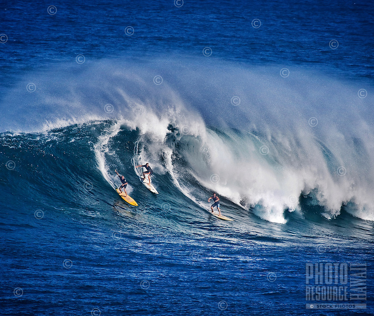 Three surfers at Waimea Bay enjoying one of the most spectacular surfing spots on North Shore of Oahu.