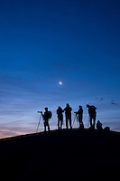 sillouhette of photographers on sand dunes at dawn