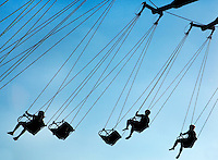 Riders on the YoYo twirling swing campaign are silhouetted against the blue Carolina skies at Carowinds, a Cedar Fair Entertainment Company amusement / theme park. Carowinds is a 122-acre theme park / entertainment / amusement park located on the state line between North and South Carolina near Charlotte, NC.