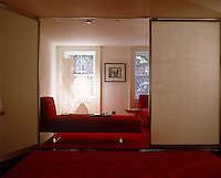 The living room is furnished with red carpets and matching upholstered day beds and can be divided by a pivoting partition wall
