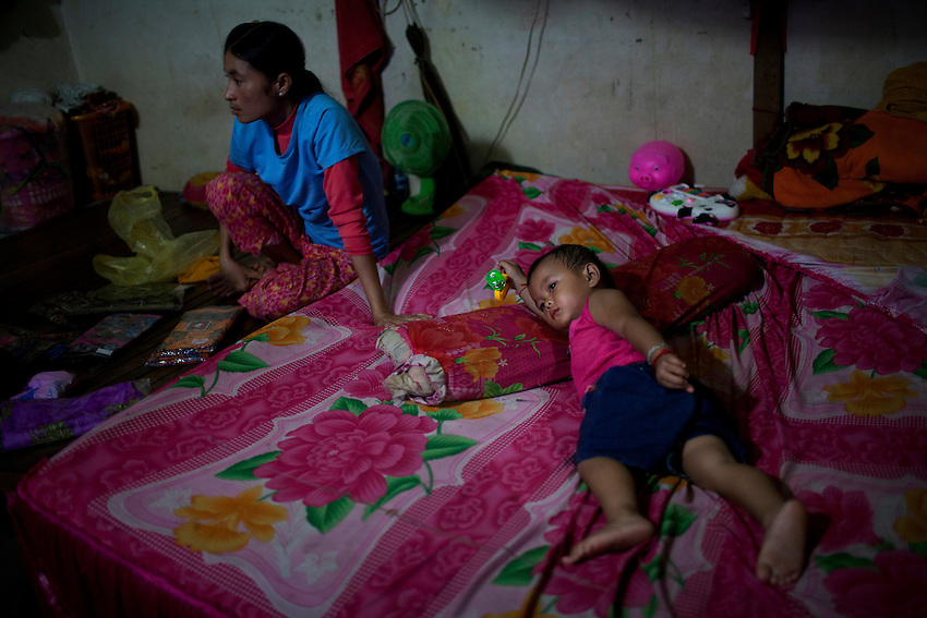 "Sorn Sreynoun, a 30-year-old worker at the Shen Zhou garment factory, sits with her nephew in her rented room, which she shares with her sister, her sister's husband, and her nephew, Phnom Penh, Cambodia, Sept 14, 2011. Sorn Sreynoun has been working at Shen Zhou since 2005. Every six months she receives a new short-term contract, but there is no increase in the fixed salary (US$61 per month). She says she can earn around US$120 per month with overtime. The room costs US$40 per month, but she says before the salary increase in October 2010, it was cheaper. ""The price of the rented room always goes up when the fixed salary increases,"" she said ""It was US$30 before last October, then it went up to $35 and now it is $40 per month (after the rent was increased again a couple of months ago)."" Sorn Sreynoun spends around $30 dollars on food per month, and gets rice from her mother in their home province. ""The amount I spend depends on how much I eat and what kind of food. If I eat more delicious food, I will spend more."" She said ""If I eat less, my health will not be good and I won't be able to work properly. But if I eat more, I won't have money."" She has a 9-year-old son (who she sends money to support) living with her mother in Prey Veng province. Previously she was married, but her husband died 6 years ago, which is why she decided to get a job at a factory. ""Shen Zhou rarely has demonstrations because there are few problems. When we have problems, the workers will talk to our workers representative,"" she said."