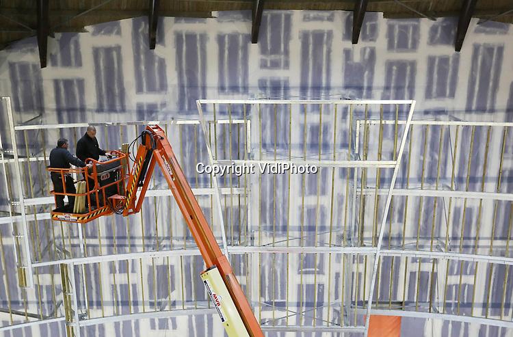 Foto: VidiPhoto<br /> <br /> HARDERWIJK - Personeel van staalconstructiebedrijf Van de Kamp uit Barneveld, werkt op dit moment aan een enorm 3D videoscherm in de Koepel van het Dolfinarium in Harderwijk. Het karakteristieke paradepaardje van het zeezoogdierenpark ondergaat op dit moment een ingrijpende renovatie van vele miljoenen. Zowel decor, tribune en bassins in het zogenoemde DolfijndoMijn worden vernieuwd. Daarnaast krijgt het gebouw een nieuw dak vernieuwd en wordt de gehele buitenzijde geschilderd. De dolfijnen ijn verhuisd naar de DolfijnenDelta. Aan het frame voor de videoschermen wordt op dit moment hard gewerkt. Naast de 3D-mapping videoprojectie, dat verzorgd wordt door NuFormer uit Zierikzee, zal er rond de bassins een watersysteem aangelegd worden waardoor er tijdens de show gebruik gemaakt kan worden van waterstralen. Verder wordt komt er een systeem voor het maken van waternevel, waar vervolgens beelden op worden geprojecteerd. Het Dolfinarium is zelf hoofduitvoerder, met als aannemer Van de Kolk uit Garderen. Op 27 april moet alles klaar zijn.