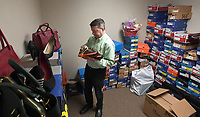 NWA Democrat-Gazette/J.T. WAMPLER Steven Hinds, vice president of philanthropy and development at Ozark Guidance Center, sorts Thursday April 12, 2018 through some of the 2,000 pairs of shoes for the center's eighth annual Walk a Mile in My Shoes sale of new and nearly new shoes and handbags  at the Northwest Arkansas Holiday Inn Atrium in Springdale. The VIP pre-sale is at 5:30 today ((Friday)), and doors open to sale at 6:30 p.m. The event continues tomorrow ((Saturday)) from 8-11 a.m. Tickets are available at the door or by visiting the center's website at http://www.ozarkguidance.org/