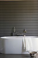 In the bathroom an antique pewter bowl creates an interesing counterpoint to the sleek and elegant modern bath