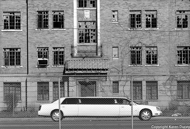 """A limousine in town for the Miss USA Beauty Pageant passes by one of Gary's many dilapidated buildings.  In an effort to improve the city 253 buildings were demolished last year. """"The city may not have been ready"""" explains Richard Grey, managing editor of the local paper the Post-Tribune, """"but if you wait until you're ready you're never gonna have these things.""""..."""