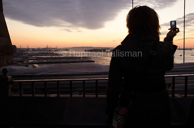 December 12, 2011. A woman taking a photo with her phone from the Brooklyn Bridge.